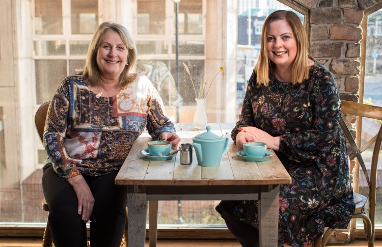 Emma Liddle and Una Coulson sitting at a table drinking coffee
